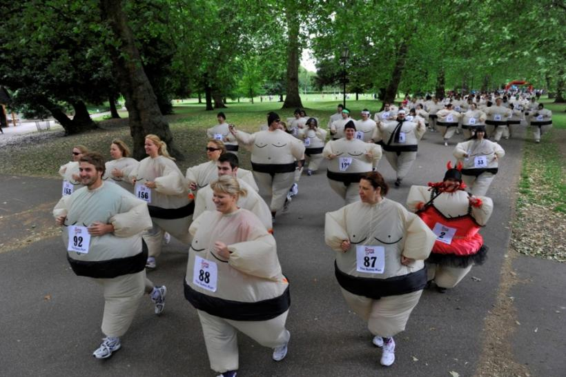 Runners dressed in inflatable Sumo costumes take part in a charity 5km (3 miles) run at Battersea Park in London