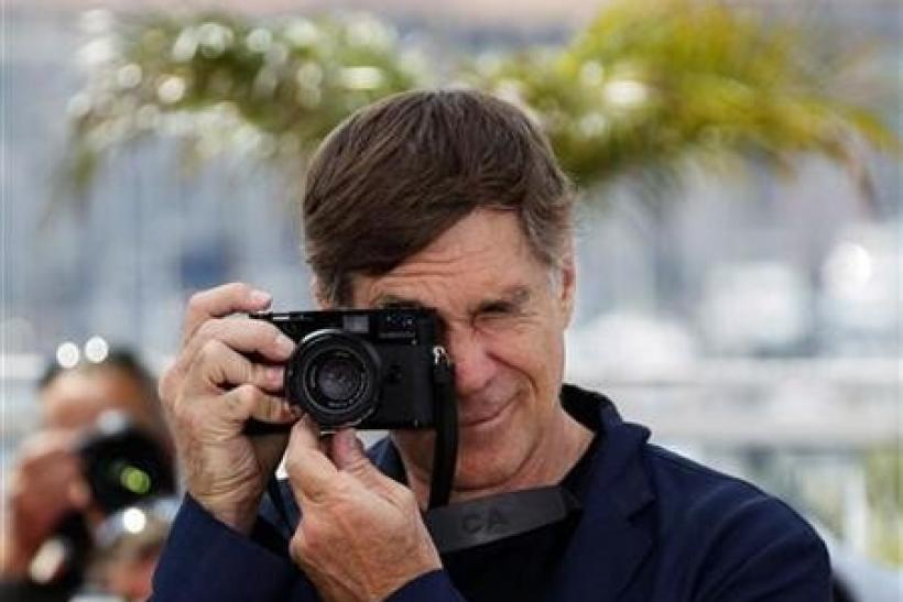 Director Gus Van Sant takes pictures during a photocall for the film ''Restless'' in competition for the category ''Un Certain Regard'' at the 64th Cannes Film Festival