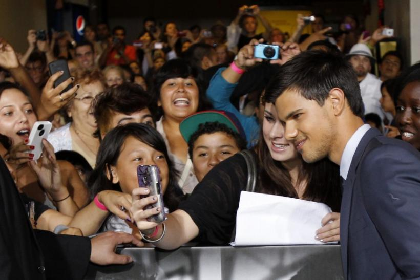 "Cast member Taylor Lautner poses with a fan during the world premiere of ""Abduction"" at the Grauman's Chinese theatre in Hollywood, California"