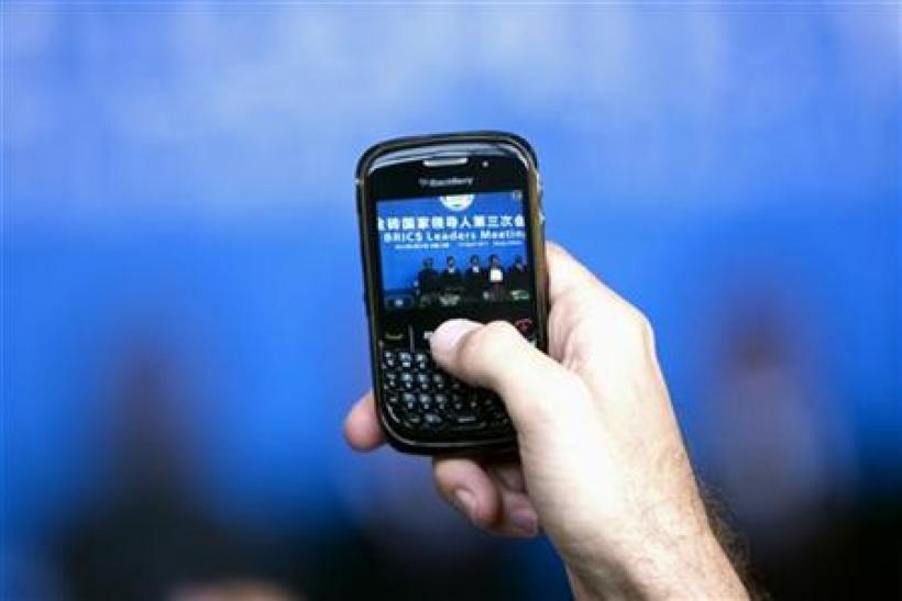 A man uses a Blackberry mobile phone to take a picture of leaders of the BRICS during a joint news conference in Sanya