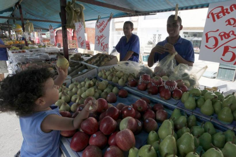 A child holds a pear in front of vendors at Feira Livre market on a streets of Vila Madalena neighbourhood in Sao Paulo