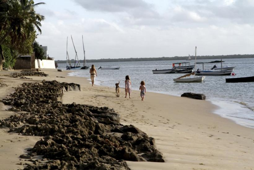 Tourists walk along the beach at Kiwayu Safari Village resort, north of Lamu