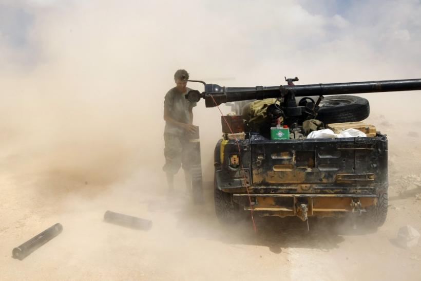 An anti-Gaddafi fighter loads a cannon near Sirte, the hometown of deposed leader Muammar Gaddafi