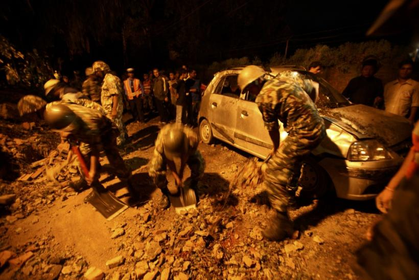 Members of the Nepalese army clear stones around a damaged car after the wall surrounding the British Embassy collapsed on top of the car that was passing by in Kathmandu