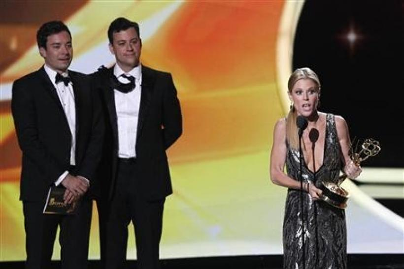 Actress Julie Bowen from television series ''Modern Family'' accepts the award for Outstanding Supporting Actress in a Comedy Series as presenters Jimmy Kimmel (L) and Jimmy Fallon look on, at the 63rd Primetime Emmy Awards in Los Ange