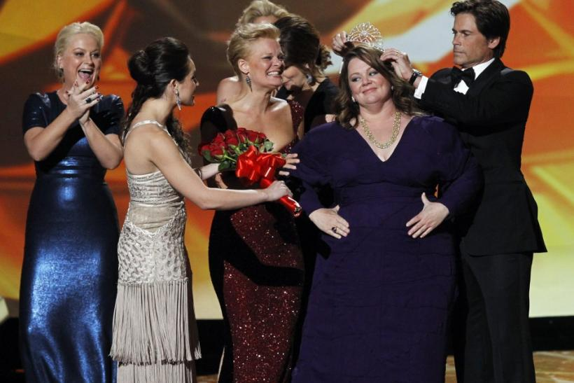 "Melissa McCarthy of ""Mike and Molly"" accepts a tiara and the award for outstanding lead actress in a comedy series from presenter Rob Lowe (R) and fellow nominees Amy Poehler (L) and Martha Plimpton (C) at the 63rd Primetime Emmy Awards in Los A"