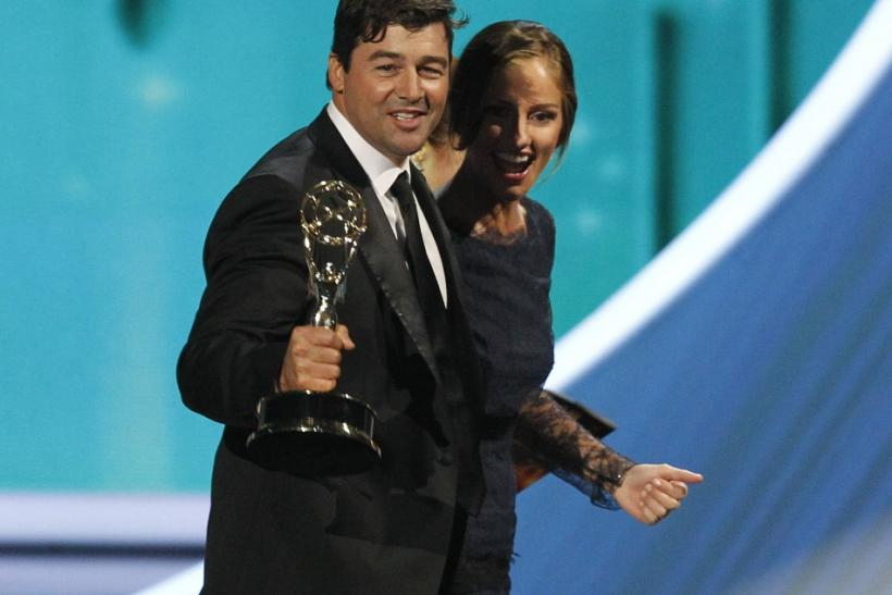 "Actor Kyle Chandler walks offstage with presenter Minka Kelly after accepting outstanding lead actor in a drama series for ""Friday Night Lights"" at the 63rd Primetime Emmy Awards in Los Angeles"