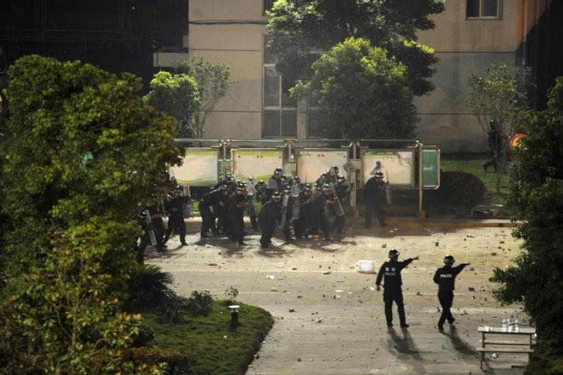 Riot policemen shield themselves from rocks thrown by protesters they approach the entrance of a factory in Haining