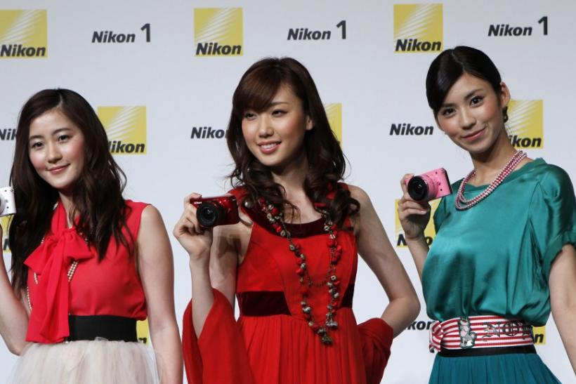 Models pose with Nikon Corp's new camera Nikon 1 J1 at its unveiling ceremony in Tokyo