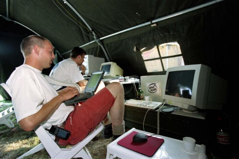 Dutchmen Jacco van Koll (L) and Luc Janssen work on their computers as they enjoy the shade of their tent during the international open-air Hacking in Progress conference in Almere, August 8.