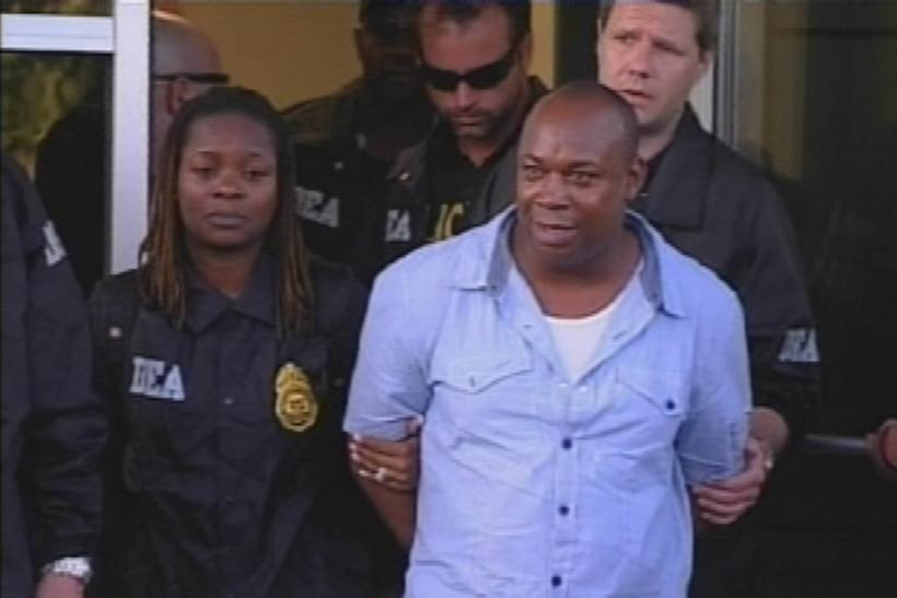 "Alleged drug kingpin Christopher ""Dudus"" Coke is escorted out of Westchester County Airport in New York"