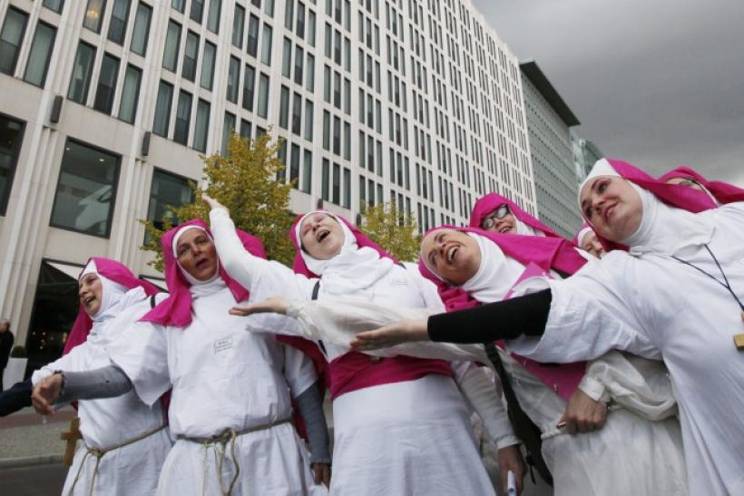 Demonstrators opposing the visit of Pope Benedict XVI sing songs during a protest at Potsdamer Platz in Berlin