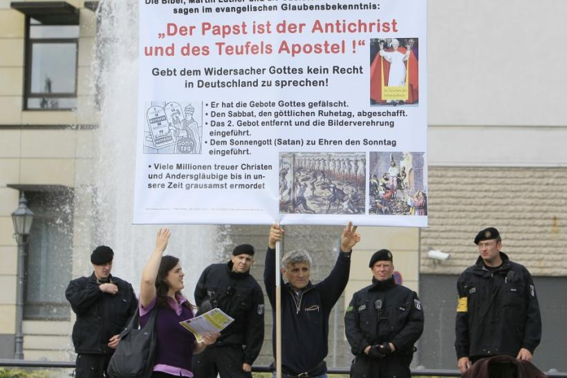 Demonstrator opposing the visit of Pope Benedict XVI holds signboard during a protest at Potsdamer Platz in Berlin