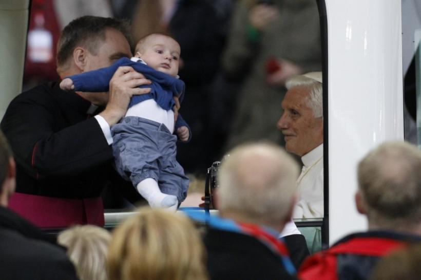 Pope Benedict XVI blesses baby from Pope Mobile as he arrives to lead Holy Eucharist celebration at Olympic Stadium in Berlin