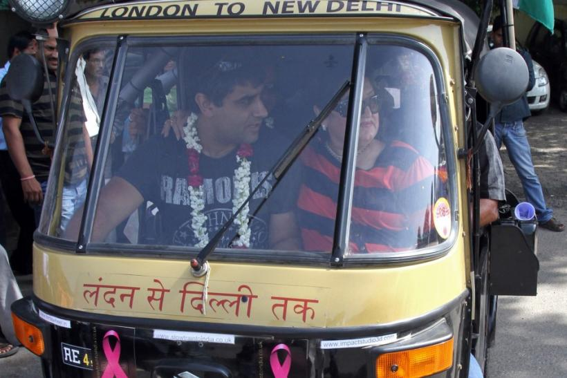"Sharma drives ""Flying Rani,"" a black-and-yellow auto rickshaw with a 175 cc engine, through a street in New Delhi"