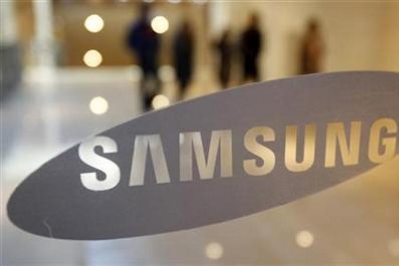 Visitors walk behind a logo of Samsung Electronics in Seoul