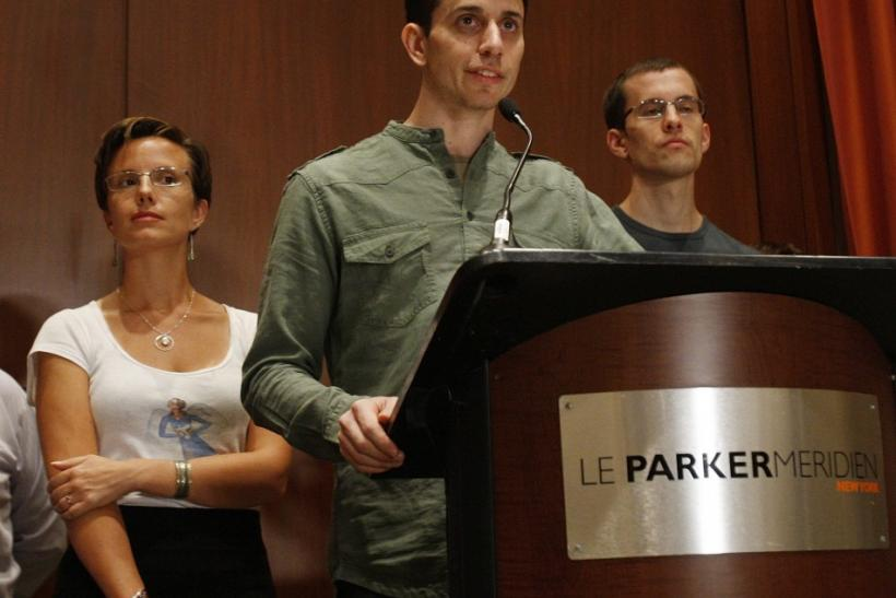 Sarah Shourd looks up at Josh Fattal as he delivers a statement about his release from detention in Iran with Shane Bauer at a news conference in New York September 25, 2011