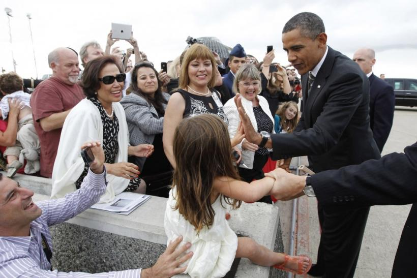 U.S. President Barack Obama high-fives with a girl a upon his arrival in San Jose, California