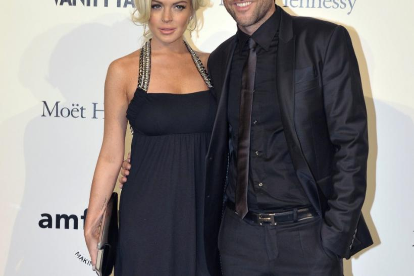 Actress Lindsay Lohan and designer Philippe Plein arrive at the amfAR's Milan Fashion Week Gala in Milan
