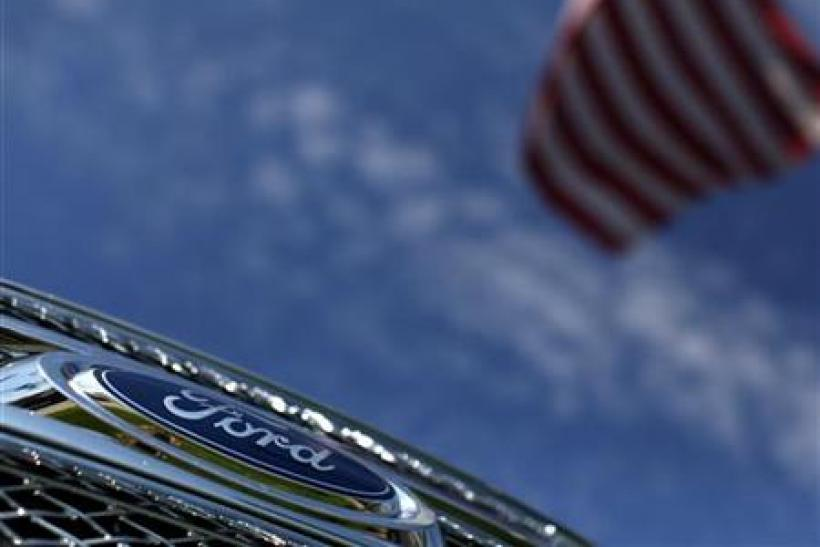 A Ford truck sits for sale under an American flag at a dealership lot in Encinitas, California
