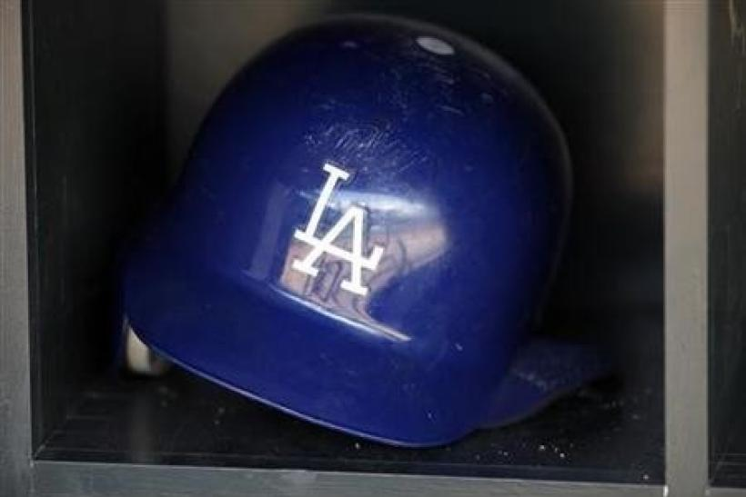 A batting helmet reflects the dugout of the Los Angeles Dodgers before the start of the Dodgers' American League baseball game against the Minnesota Twins at Target Field in Minneapolis
