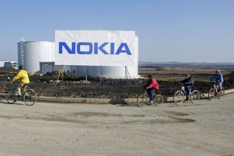 Children ride their bicycles past a billboard near the entrance of the new Nokia plant in Jucu village