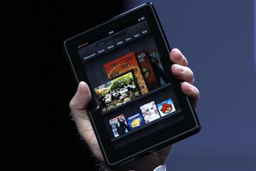 Jeff Bezos holds up the new Kindle Fire at a news conference during the launch of Amazon's new tablets in New York