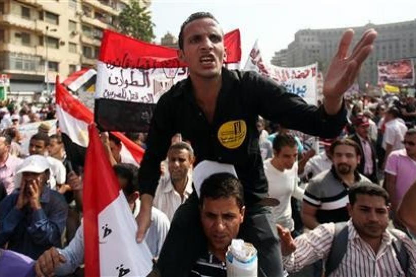 Protesters chant slogans against the government and military rulers at Tahrir Square after Friday prayers in Cairo