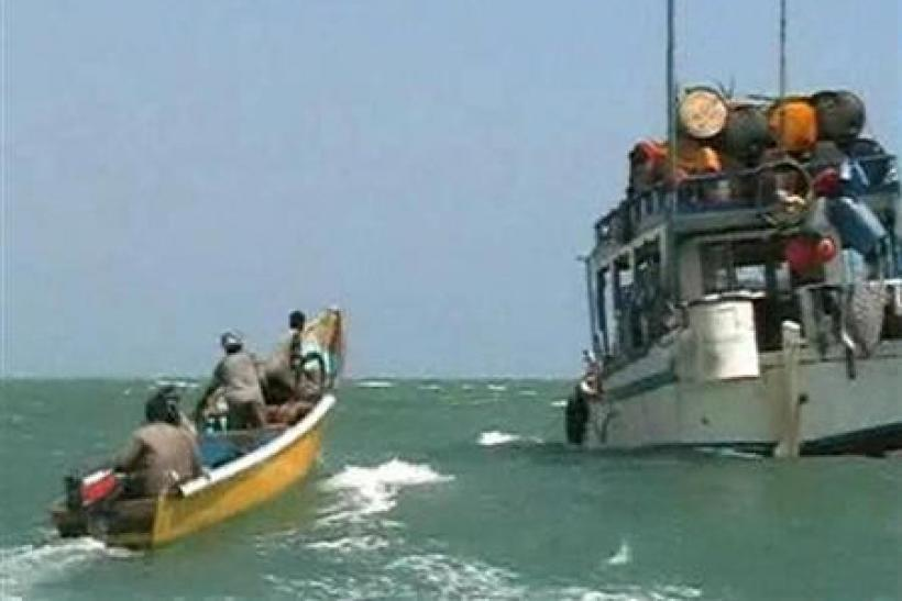 Pirates on speedboat approach one of their mother boats docked near Eyl, Somalia