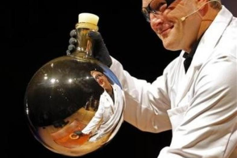 A chemist is reflected in a beaker after mixing chemicals that gave the beaker a reflective coating during a demonstration at the 21st annual Ig Nobel prize ceremony at Harvard University in Cambridge, Massachusetts