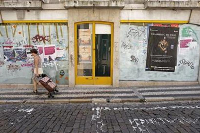 A woman pulls her shopping trolley in front of a closed shop in central Lisbon