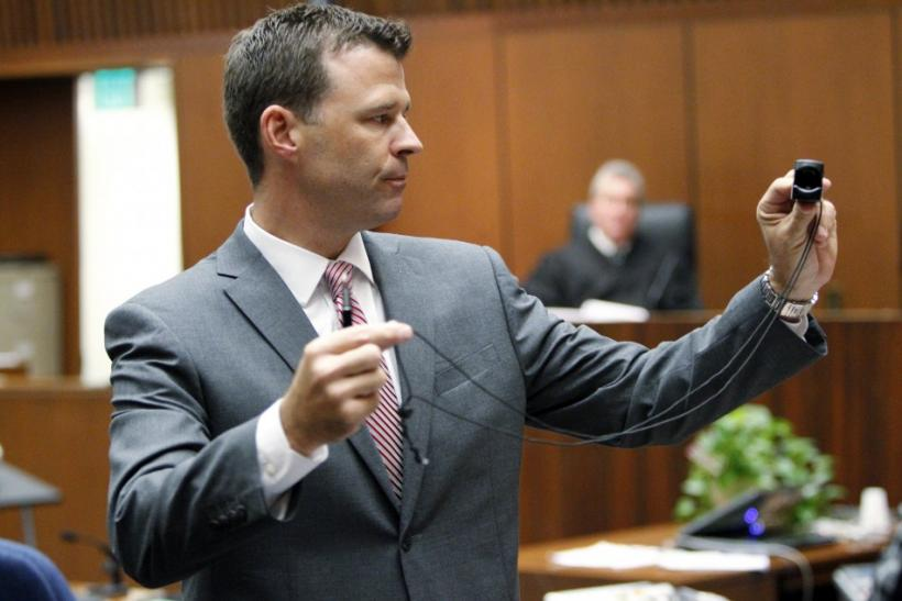Deputy District Attorney David Walgren holds a monitoring device introduced as evidence as he questions Alberto Alvarez, one of Michael Jackson's security guards, during Dr. Conrad Murray's trial in the death of pop star Michael Jackson in Los Angeles
