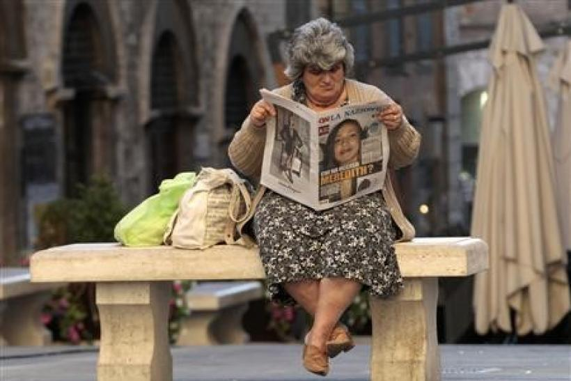 A woman reads a newspaper reading ''Who killed Meredith ?'' in Perugia