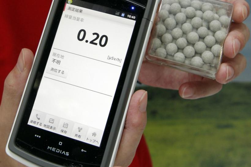 A staff member of NTT DoCoMo holds a prototype of a smart phone case which measures radiation levels as demonstrated on radium balls (R) which contains a small amount of radiation at the CEATEC JAPAN 2011 electronics show in Chiba, east of Tokyo