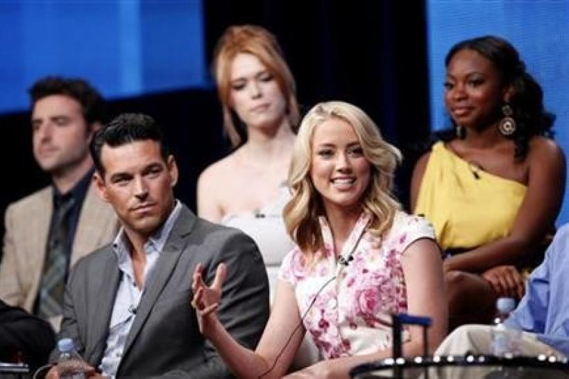 Cast member Amber Heard speaks as co-stars Eddie Cibrian (L), David Krumholtz (L back), Leah Renee Cudmore and Naturi Naughton watch during the NBC Universal session for ''The Playboy Club'' at the 2011 Summer Television Critics Associ