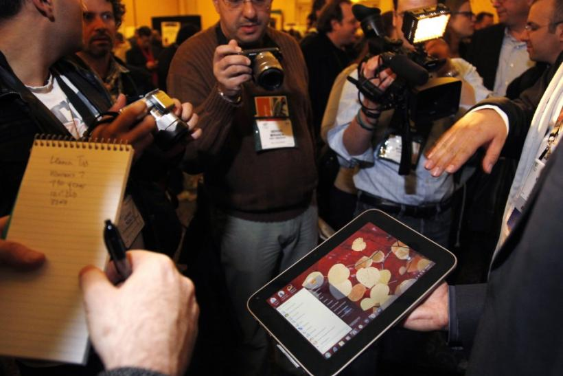 A man displays an unannounced Lenovo tablet computer at a preview of the CES in Las Vegas