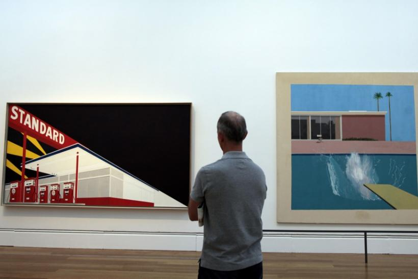 "A man views ""Standard Station"" by Ed Ruscha and ""A Bigger Splash"" by David Hockney at the ""Pacific Standard Time: Art in L.A. 1945-1980"" exhibition at the Getty Center in Los Angeles, California"