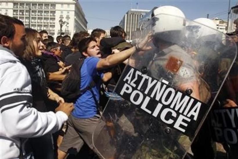 High-school students clash with riot police during a protest march against economic austerity and planned education reforms in Athens
