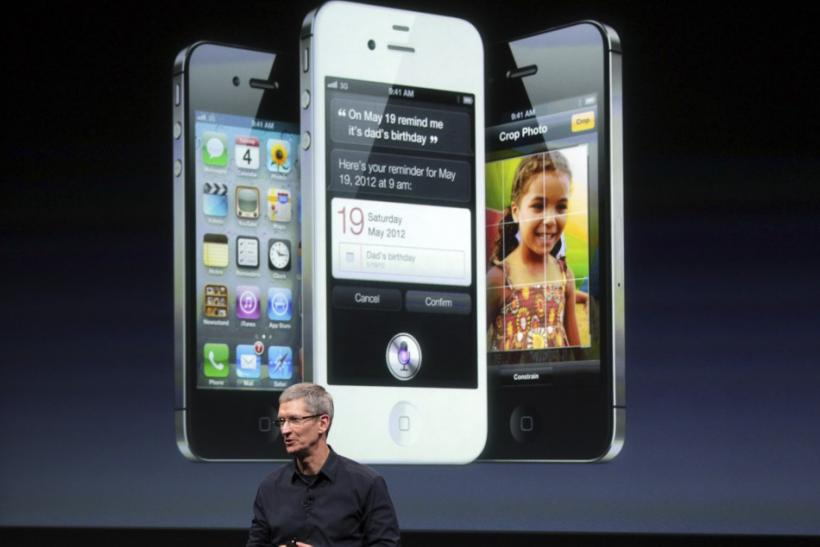 Apple CEO Tim Cook speaks in front of an image of an iPhone 4S at Apple headquarters in Cupertino, California