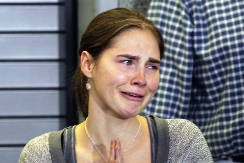 Amanda Knox cries and gestures to friends during a news conference at Sea-Tac International Airport, Washington