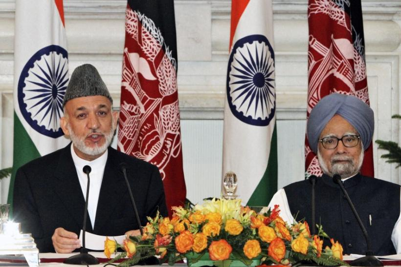 Afghanistan's President Karzai speaks with the media as India's Prime Minister Manmohan Singh watches after signing a joint statement at Hyderabad House in New Delhi