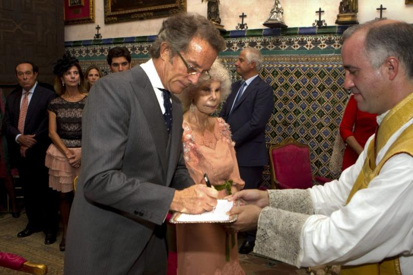 Spain's Duchess of Alba Cayetana Fitz-James Stuart y Silva looks on as her husband Alfonso Diez sign a document during their wedding ceremony in Seville