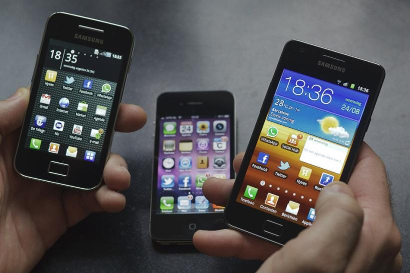 A man holds a Samsung S II and a Samsung Ace next to an Apple iPhone 4. Samsung may end up releasing its two iPhone killers in October, the same month Apple plans to release the iPhone 4S.