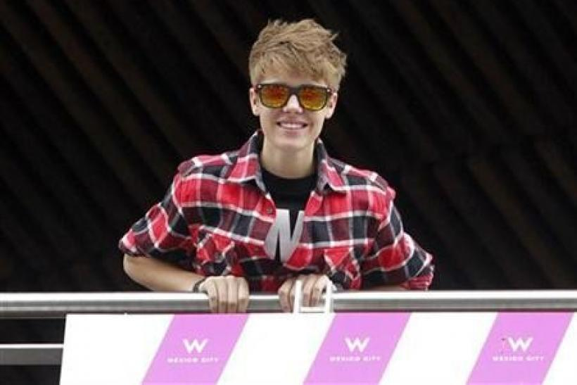 Canadian pop singer Justin Bieber greets his fans from the balcony of his hotel in Mexico City