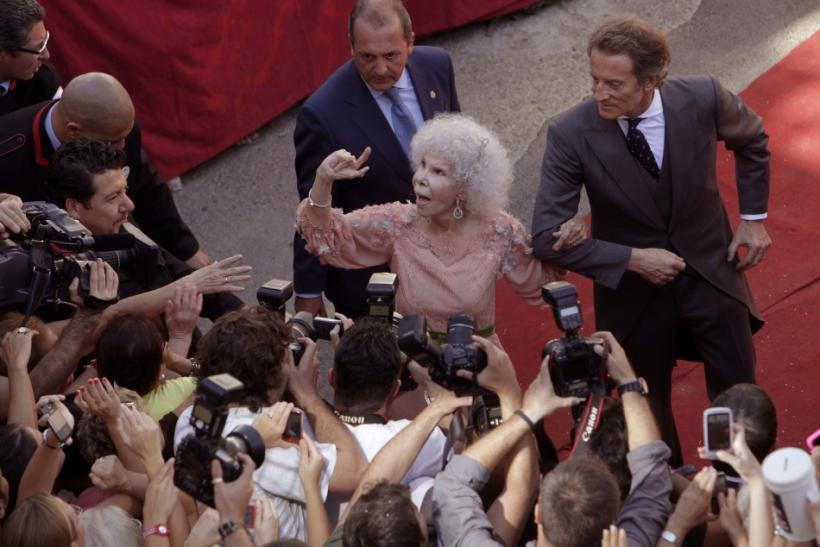 Spain's Duchess of Alba Cayetana Fitz-James Stuart y Silva (L) and her husband Alfonso Diez greet the crowd outside Las Duenas Palace after their wedding in Seville