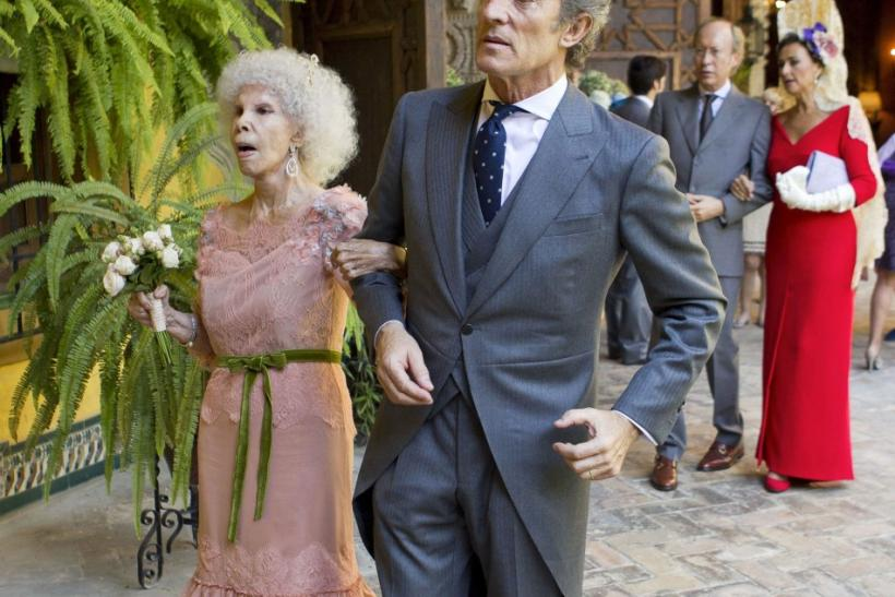 Spain's Duchess of Alba Cayetana Fitz-James Stuart y Silva (L) and her husband Alfonso Diez walk inside Las Duenas Palace after their wedding ceremony in Seville
