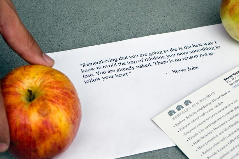 A man places an apple next to a quote by Steve Jobs on the floor of an Apple store in Berkeley, California