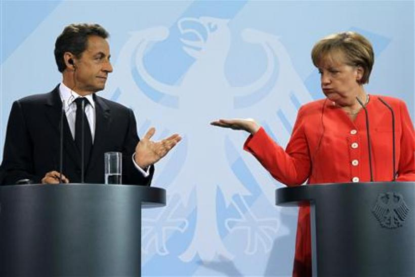 French President Nicolas Sarkozy (L) and German Chancellor Angela Merkel gesture as they address a news conference at the Chancellery in Berlin
