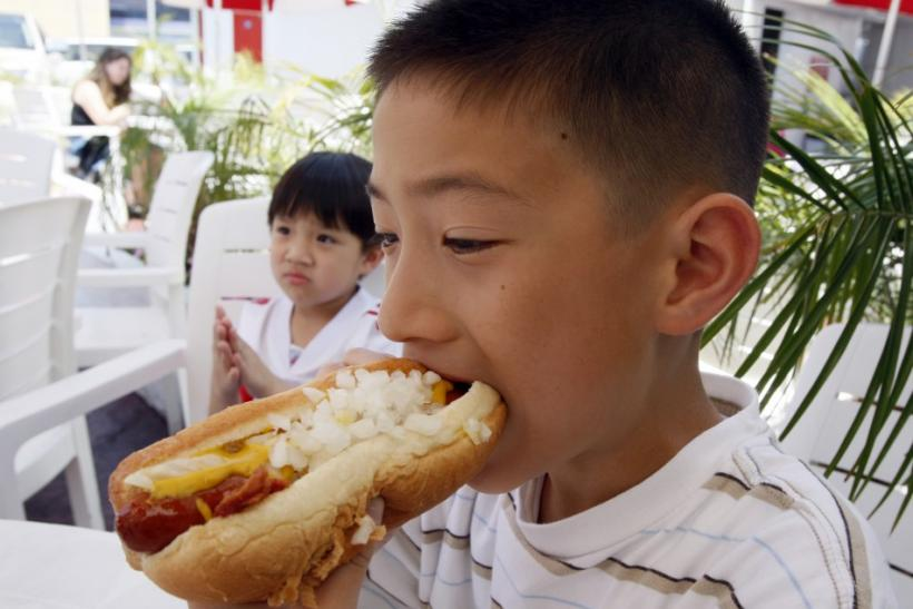 Martin Nguyen takes a bite of a hot dog at Pink's in Hollywood, California