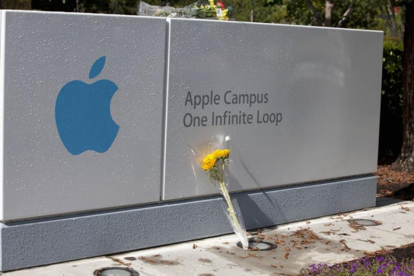A bouquet of flowers in honor of the passing of former Apple CEO Steve Jobs lies in front of the sign of Apple headquarters in Cupertino, California